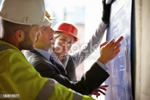 istock Professional construction workers reviewing building plans 180815577