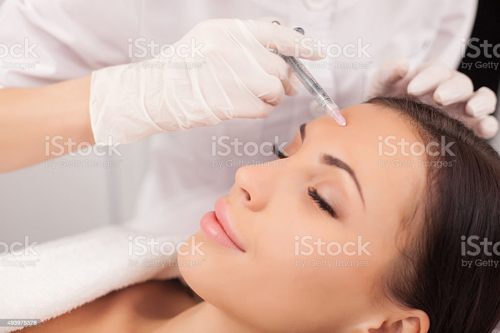 Professional cosmetologist is making procedure at clinic stock photo