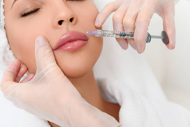 professional cosmetologist making facial injection - injection de toxine botulique photos et images de collection