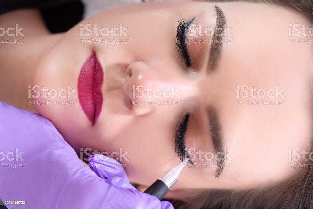 Professional cosmetologist wearing purple gloves making permanent eyeliner - Royalty-free Adulto Foto de stock