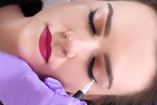 professionelle kosmetikerin lila handschuhe machen permanent eyeliner - gesicht make up anleitungen stock-fotos und bilder