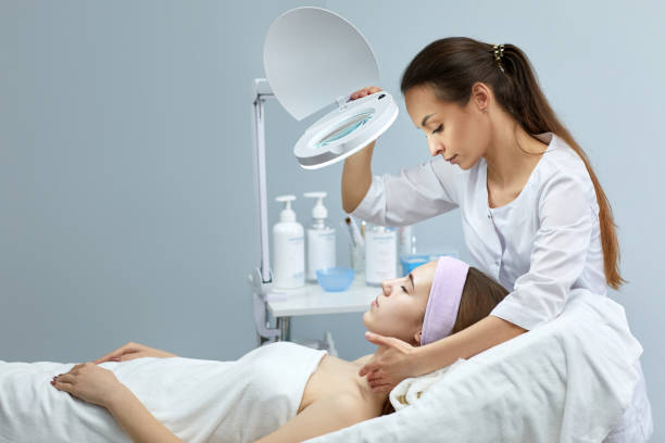professional cosmetologist with patient in clinic professional cosmetologist with beautiful woman patient in clinic dermatologist stock pictures, royalty-free photos & images