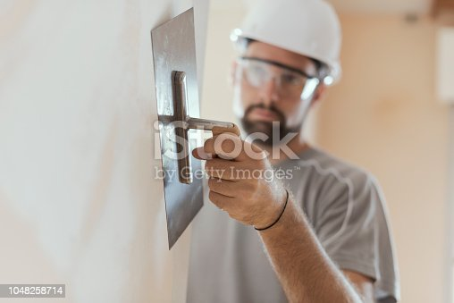 Professional craftsman applying plaster with a trowel, home renovation concept
