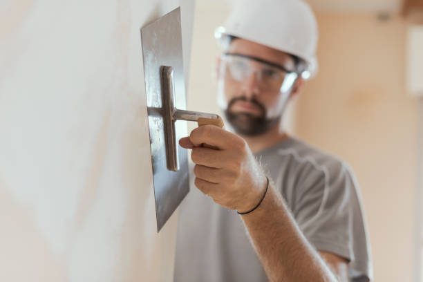 Professional craftsman applying plaster with a trowel Professional craftsman applying plaster with a trowel, home renovation concept plaster stock pictures, royalty-free photos & images