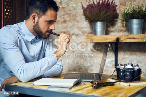 904263506 istock photo Professional creative bearded male journalist thinking over new report editing photo images made by vintage camera making illustration in retro style sitting in modern interior cafe using laptop 904262334