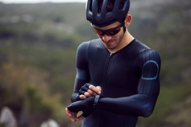 Professional cyclist checking fitness tracker on bicycle in a mountain stock photo