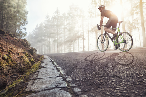 istock Professional Cyclist on a forest road 874293578
