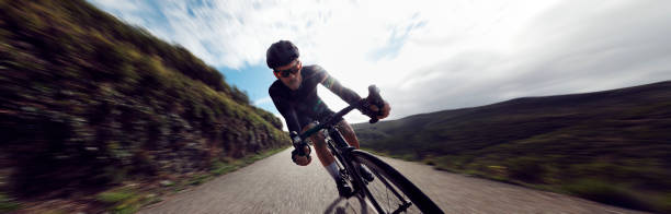 Professional cyclist riding bicycle fast on a mountain road stock photo