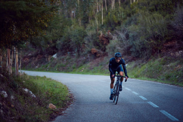 Professional cyclist riding bicycle on a forest asphalt road stock photo