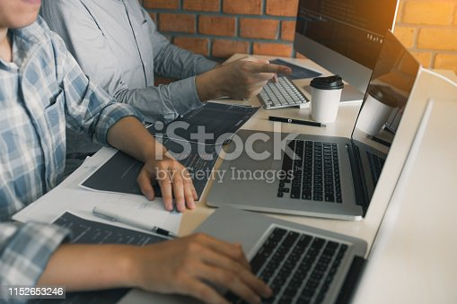 istock Professional development programmer cooperating meeting programming website working a software in office room. 1152653246
