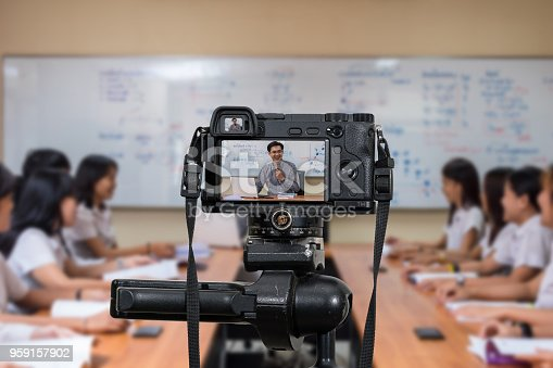 istock Professional digital Mirrorless camera on the tripod recording video blog of Asian teacher in the classroom, Camera for photographer or Video and Technology Live Streaming concept, University education concept 959157902