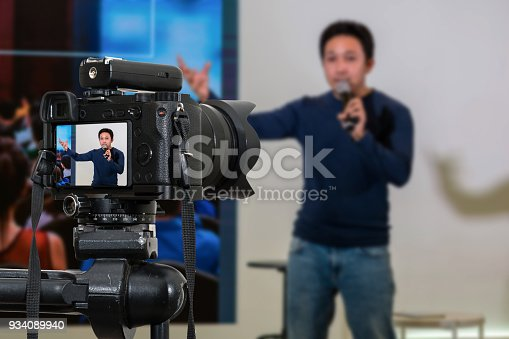 istock Professional digital Mirrorless camera with microphone on the tripod recording video blog of asian Speaker on the stage seminar, Camera for photographer or Video and Technology Live Streaming concept 934089940