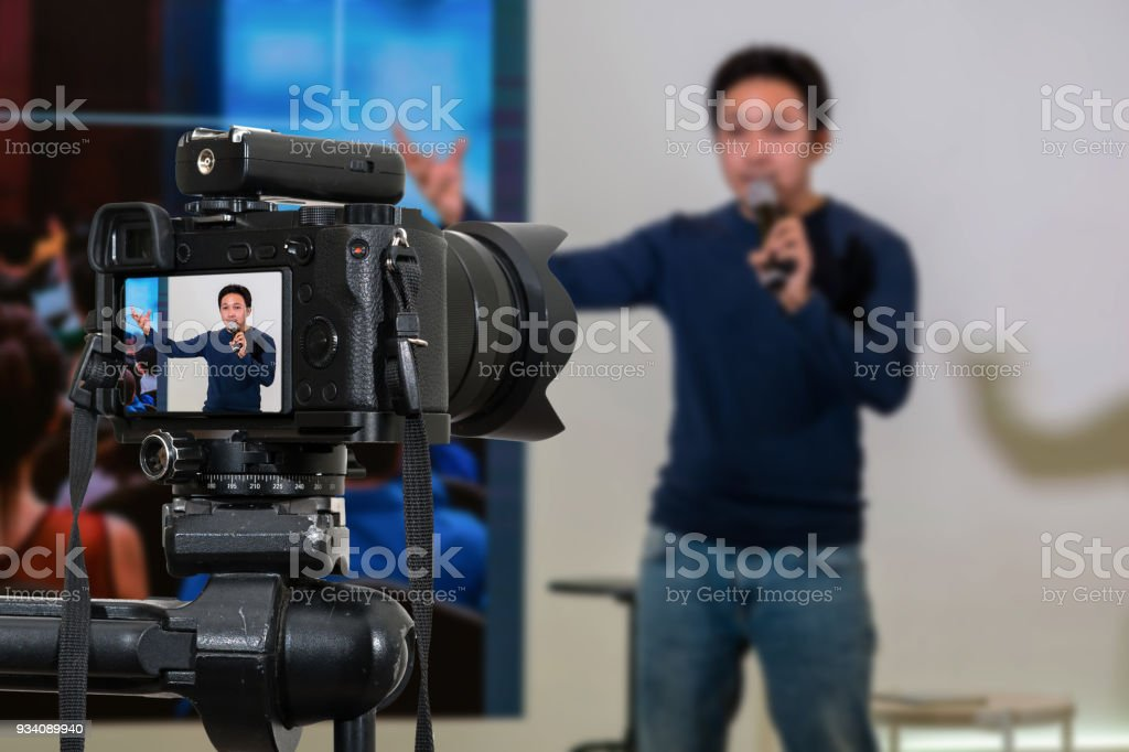 Professional digital Mirrorless camera with microphone on the tripod recording video blog of asian Speaker on the stage seminar, Camera for photographer or Video and Technology Live Streaming concept stock photo