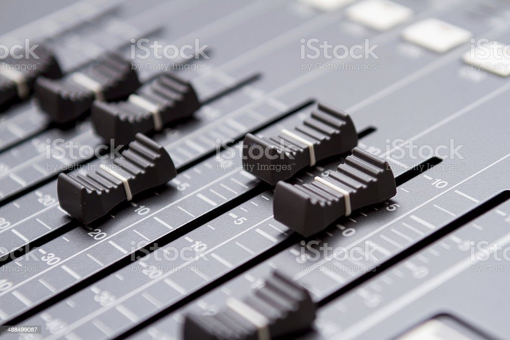 Dramatically lit detail of a new digital sound board, referred also...
