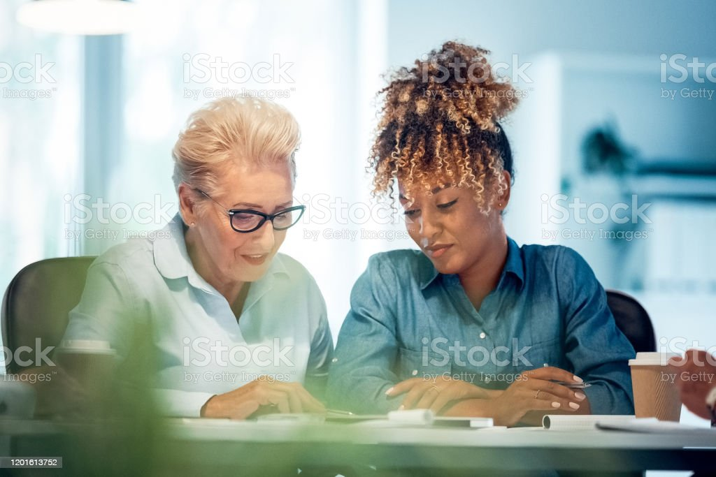 Professional discussing plan with female colleague Elderly professional discussing plan over document with female colleague. Expertise are working together in new business. They are sitting in office. 35-39 Years Stock Photo