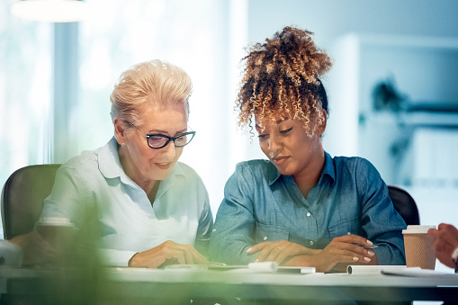 Professional Discussing Plan With Female Colleague Stock Photo - Download Image Now