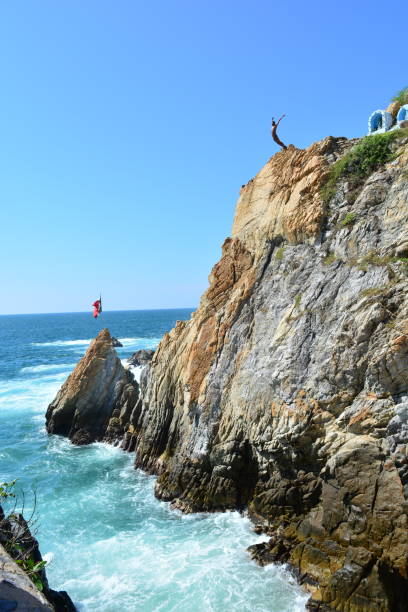 Professional diver jumping from a rock in La Quebrada Beach, Acapulco stock photo