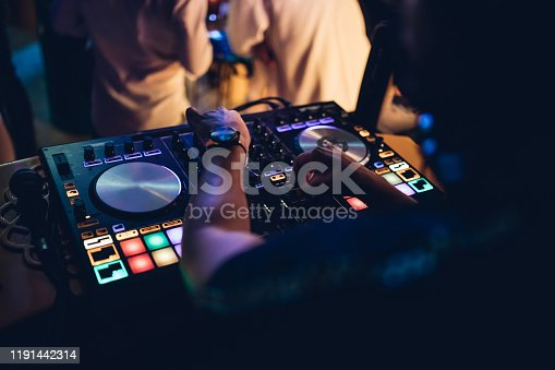 istock Professional DJ plays live set and mixing music on turntable console at stage in the beach night club. Disc Jokey Hands on a sound mixer station at club party. DJ mixer controller panel for playing music and partying. 1191442314