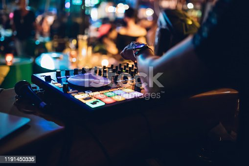 istock Professional DJ plays live set and mixing music on turntable console at stage in the beach night club. Disc Jokey Hands on a sound mixer station at club party. DJ mixer controller panel for playing music and partying. 1191450335