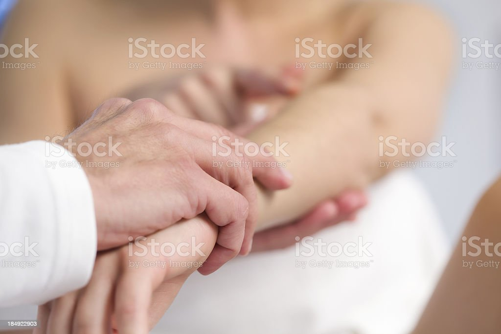 Professional doctor examining arm of a patient. stock photo