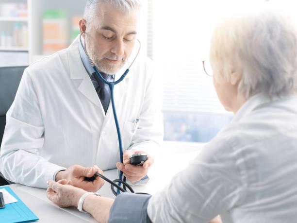 Professioneller Arzt zur Messung des Blutdrucks einer leitenden Patientin während eines Besuchs, Bluthochdruck und Präventionskonzept – Foto