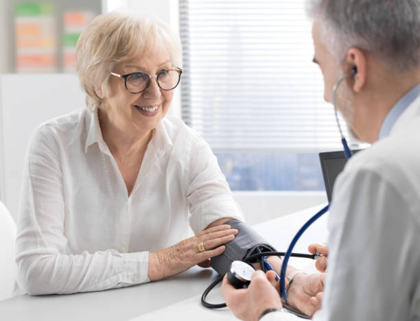 professional doctor visiting a senior patient and measuring blood pressure using a sphygmomanometer, hypertension and healthcare concept - кардиолог стоковые фото и изображения