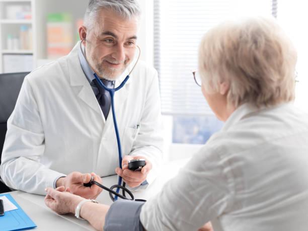 Professioneller Arzt, der einen leitenden Patienten besucht und den Blutdruck mit Hilfe eines Sphygmomanometers, Bluthochdruck und Gesundheitskonzept misst – Foto