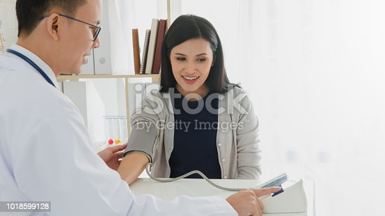 istock Professional doctor wearing white coat is checking woman patient with stethoscope and measure blood pressure in hospital background.Concept of health check in hospitals. 1018599128