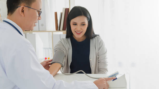 Professional doctor wearing white coat is checking woman patient with stethoscope and measure blood pressure in hospital background.Concept of health check in hospitals. Professional doctor wearing white coat is checking woman patient with stethoscope and measure blood pressure in hospital background.Concept of health check in hospitals. hypertensive stock pictures, royalty-free photos & images