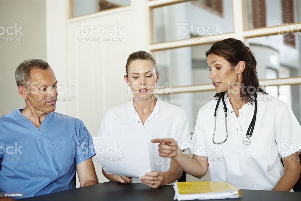 Professional doctors having a word on patience's report royalty-free stock photo