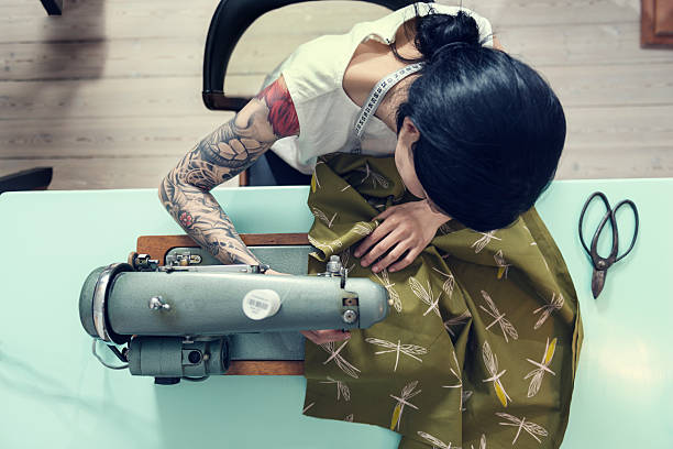 Professional Dressmaker At Work Overhead view of a female dressmaker working on a sewing machine in her design studio. Colour, horizontal format with a very shallow focus  point  on her hands as she works feeding the material through the machine. She is wearing a white sleeveless top that shows of her full sleeve tattoo she is half Japanese half european with dark hair. stitching stock pictures, royalty-free photos & images