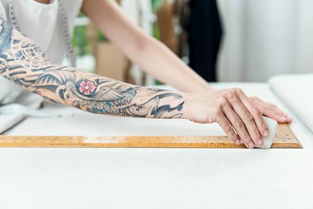 professionelle dressmaker bei der arbeit - tattoos frauen arm stock-fotos und bilder