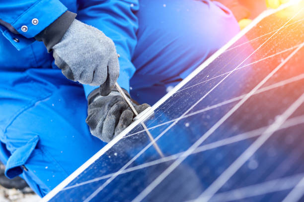 professional electrician worker installing solar panels - energia solare foto e immagini stock