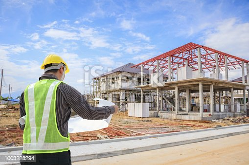 1041465228 istock photo Professional engineer architect worker with protective helmet and blueprints paper at house building construction site 1003228294
