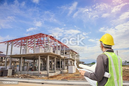 1041465228 istock photo Professional engineer architect worker with protective helmet and blueprints paper at house building construction site 1006940932
