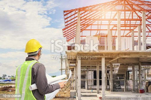 1041465228 istock photo Professional engineer architect worker with protective helmet and blueprints paper at house building construction site 1019109898