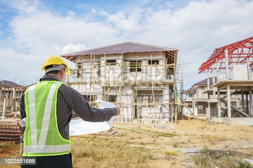 1041465228 istock photo Professional engineer architect worker with protective helmet and blueprints paper at house building construction site 1022551688