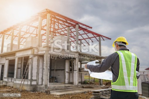 1041465228 istock photo Professional engineer architect worker with protective helmet and blueprints paper at house building construction site 1027407126