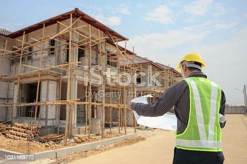 1041465228 istock photo Professional engineer architect worker with protective helmet and blueprints paper at house building construction site 1031169772