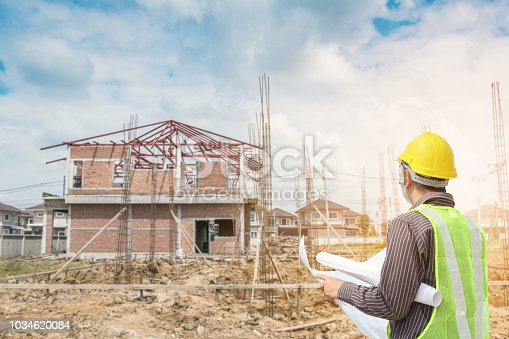1041465228 istock photo Professional engineer architect worker with protective helmet and blueprints paper at house building construction site 1034620084