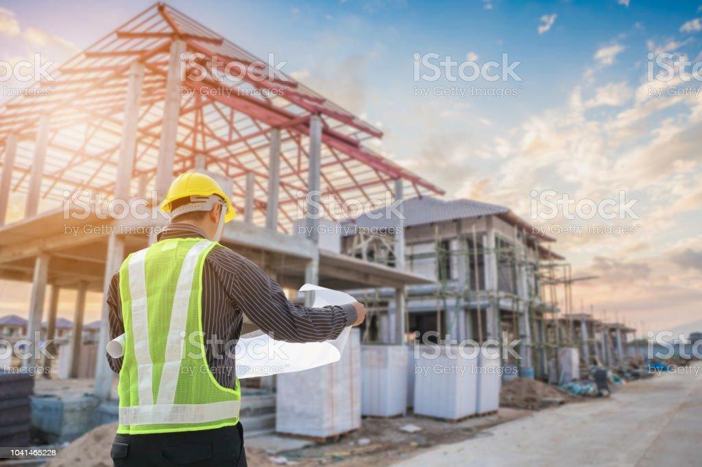 Travailleur architecte ingénieur avec le papier protecteur de casque et plans au chantier de construction de maison - Photo de Adulte libre de droits