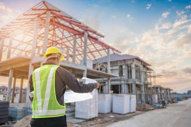 ingegnere professionista architetto operaio con casco protettivo e carta progetti nel cantiere edile della casa - costruire foto e immagini stock