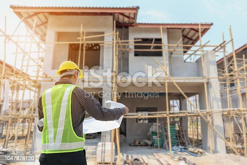 1041465228 istock photo Professional engineer architect worker with protective helmet and blueprints paper at house building construction site 1047876120