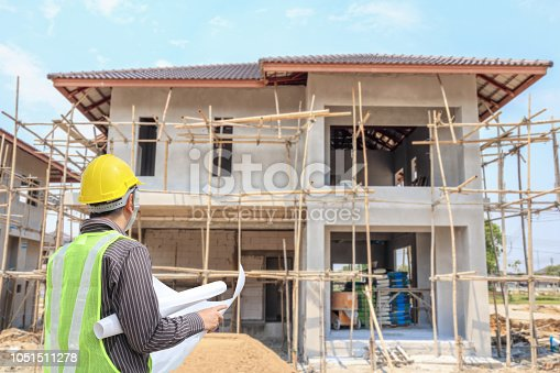 1041465228 istock photo Professional engineer architect worker with protective helmet and blueprints paper at house building construction site 1051511278