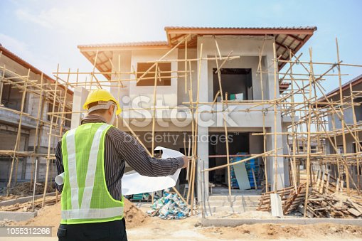 1041465228 istock photo Professional engineer architect worker with protective helmet and blueprints paper at house building construction site 1055312266