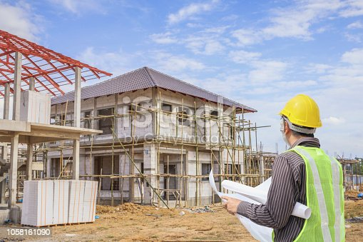 1041465228 istock photo Professional engineer architect worker with protective helmet and blueprints paper at house building construction site 1058161090