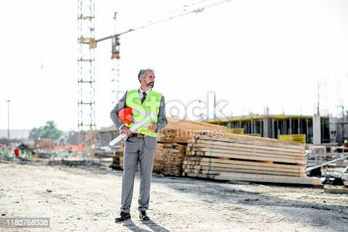 1041465228 istock photo Professional engineer architect worker with protective helmet and blueprints paper construction site 1183768338