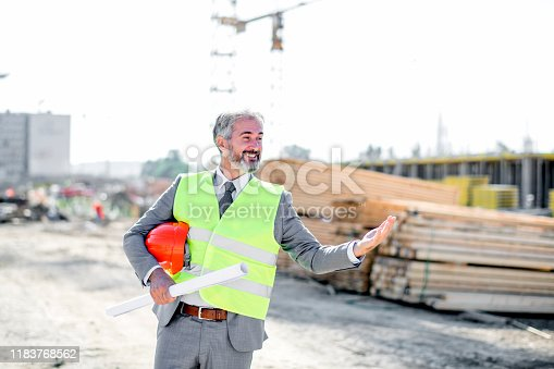 1041465228 istock photo Professional engineer architect worker with protective helmet and blueprints paper construction site 1183768562