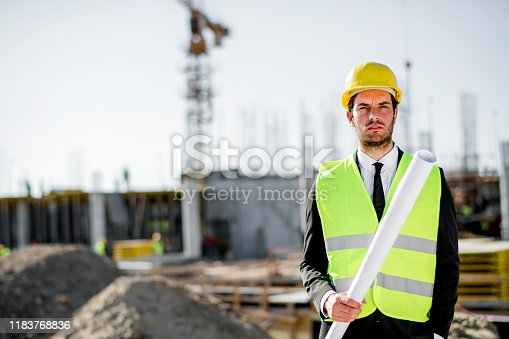 1041465228 istock photo Professional engineer architect worker with protective helmet and blueprints paper construction site 1183768836