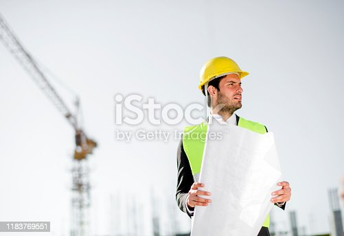 1041465228 istock photo Professional engineer architect worker with protective helmet and blueprints paper construction site 1183769551